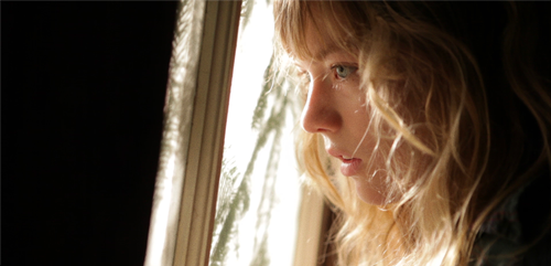 Image of a young woman looking dramatically out a window