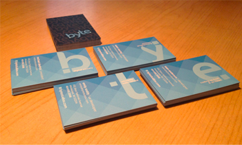 Image of business cards stacked in neat piles, showing off their designs